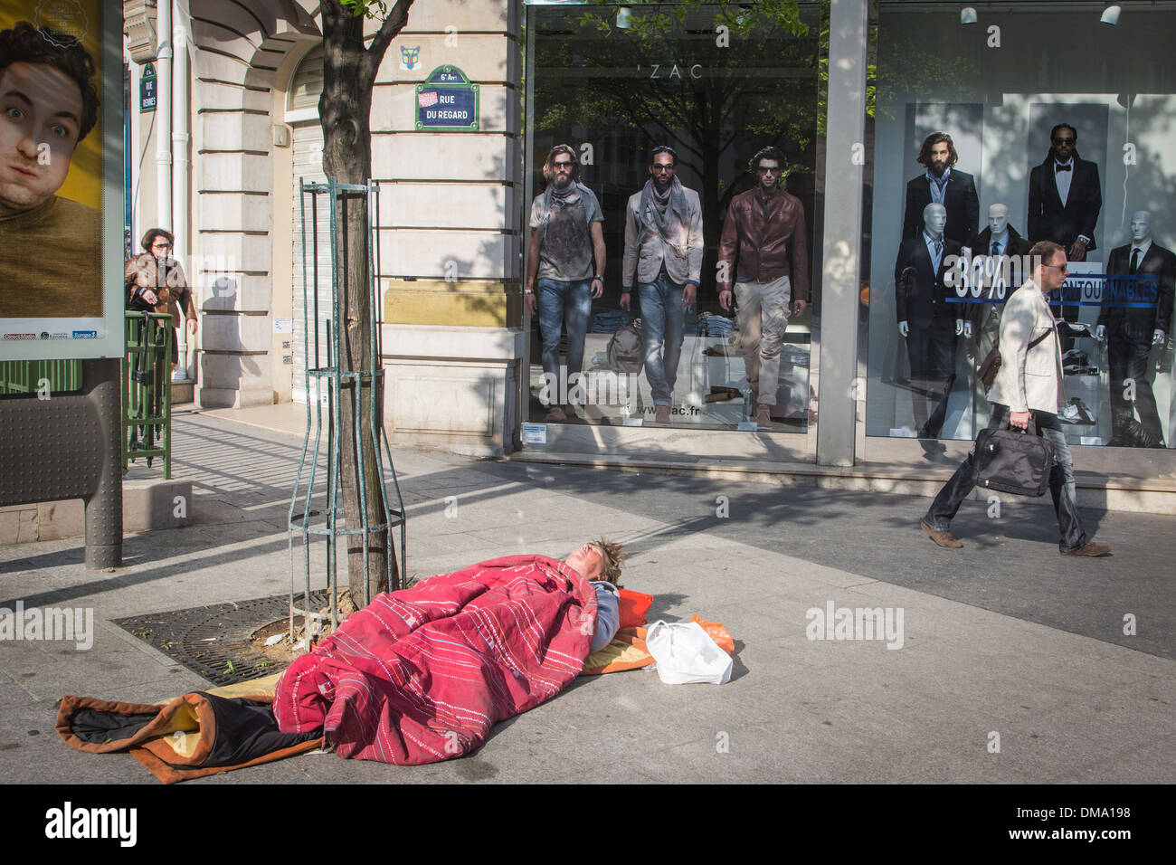 HOMELESS WOMAN LYING ON THE SIDEWALK, MISERY AND POVERTY, RUE DU REGARD, 6TH ARRONDISSEMENT, PARIS, FRANCE - Stock Image
