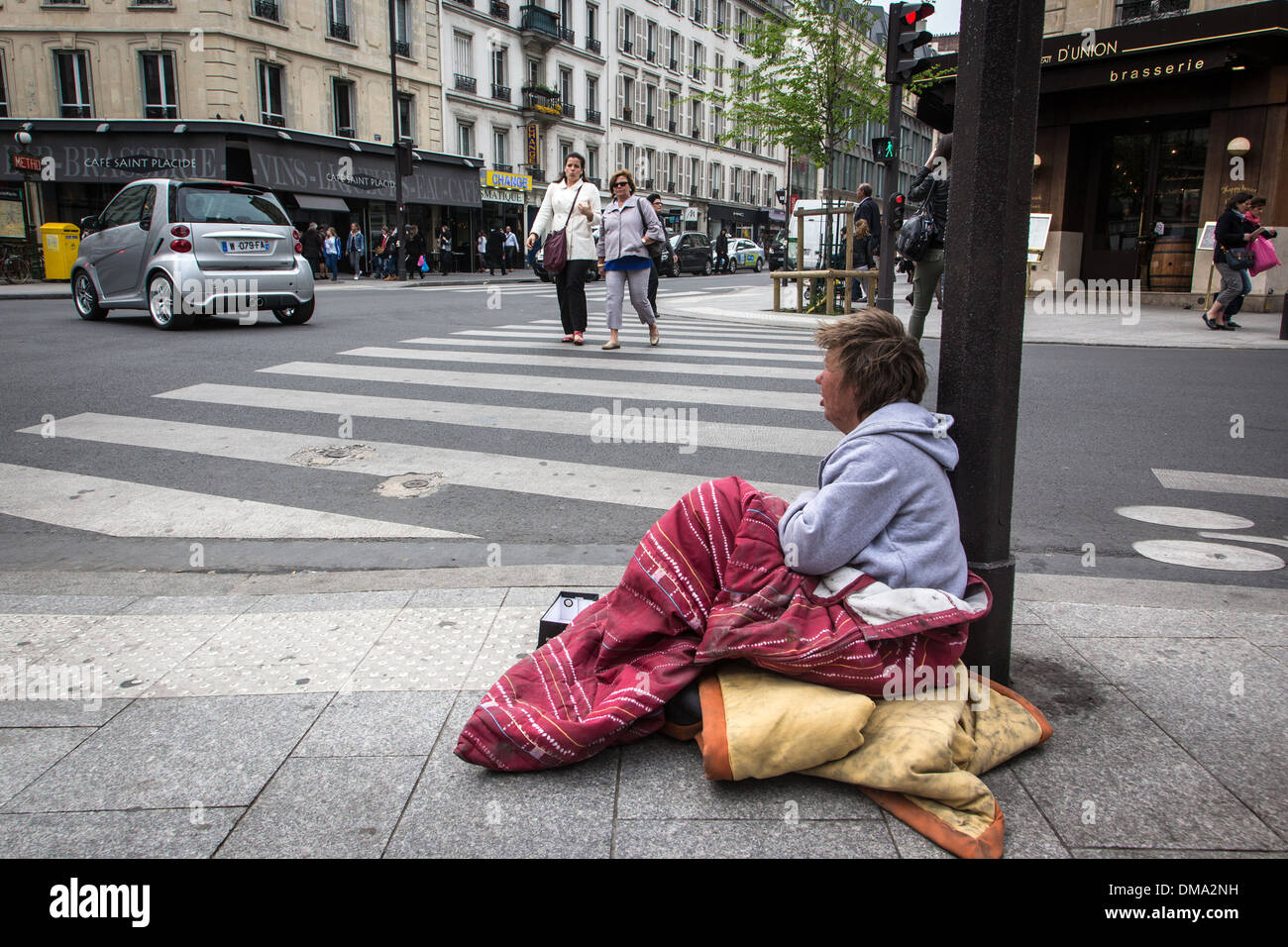 HOMELESS WOMAN LYING ON THE SIDEWALK, MISERY AND POVERTY, RUE DE RENNES, 6TH ARRONDISSEMENT, PARIS, FRANCE - Stock Image