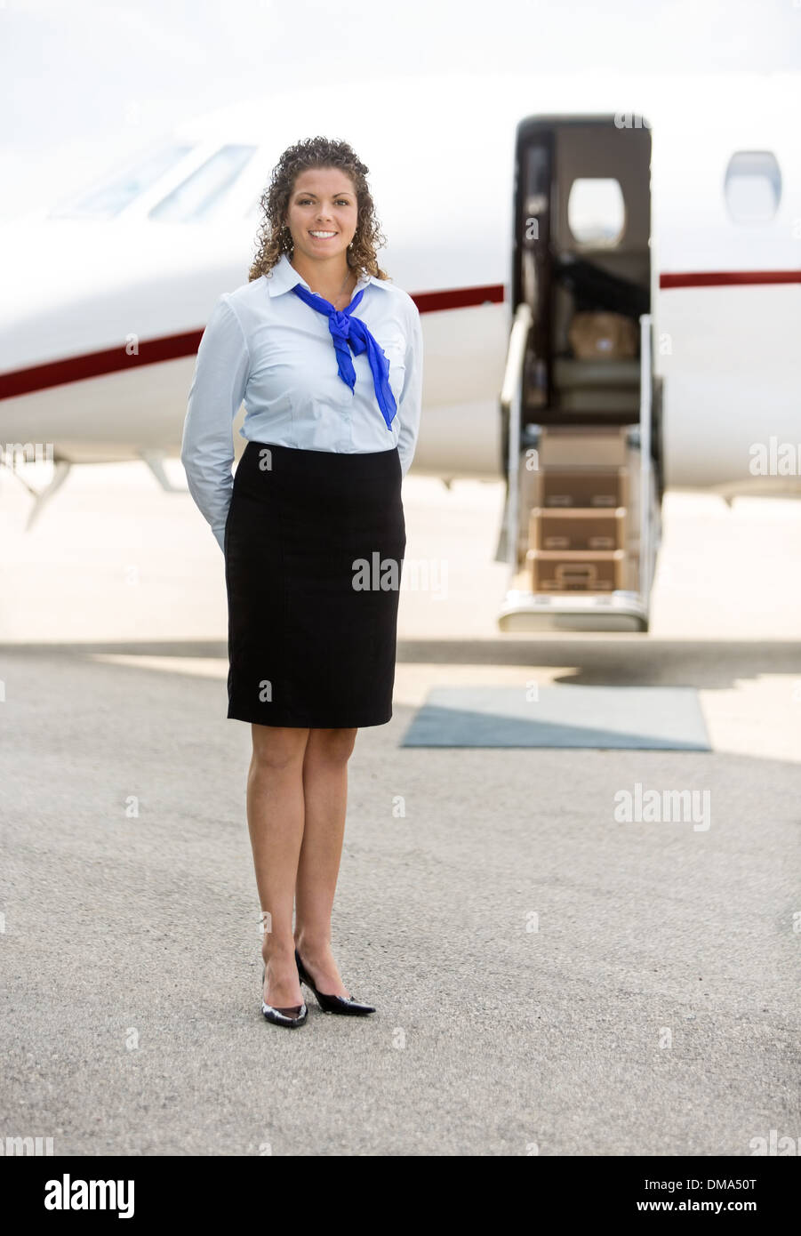 Beautiful Stewardess Standing Against Private Jet - Stock Image
