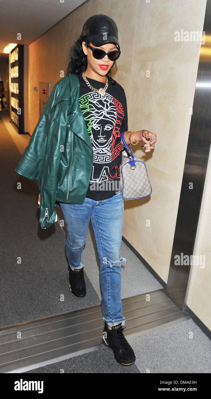 ee769c8bb Rihanna arrives at Narita International Airport wearing a Palace 'Versace' t -shirt and carrying a Gucci handbag ahead of her