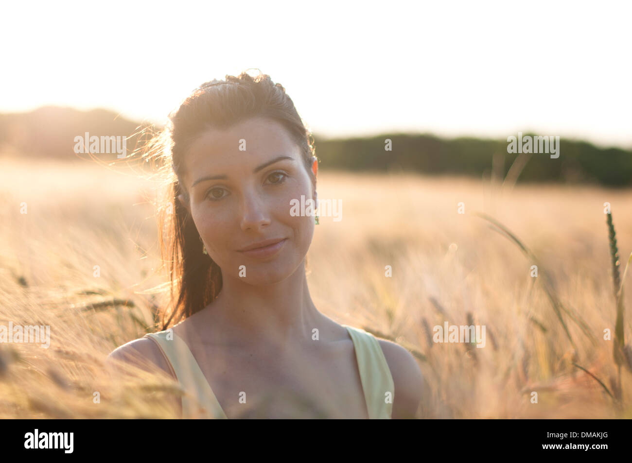 Young woman in dress standing in a corn field at sunset Stock Photo