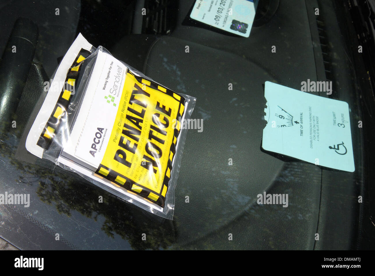A parking ticket on a car. - Stock Image