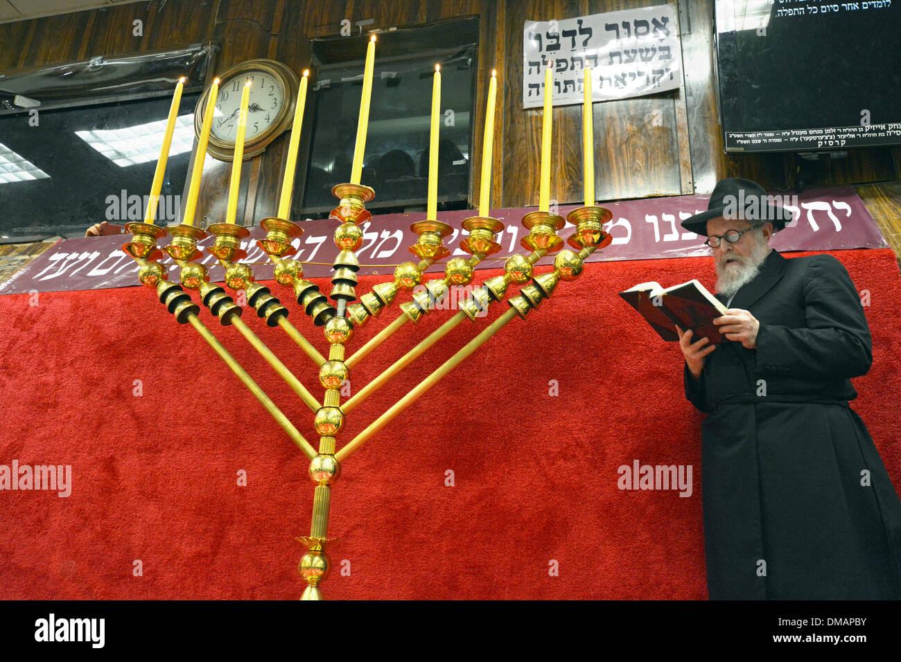 An orthodox Jewish rabbi prays after lighting Hanukkah candles at Lubavitch headquarters in Brooklyn, New York - Stock Image