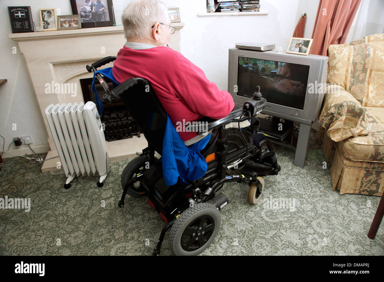 Disabled elderly man in a wheelchair watching the television - Stock Image