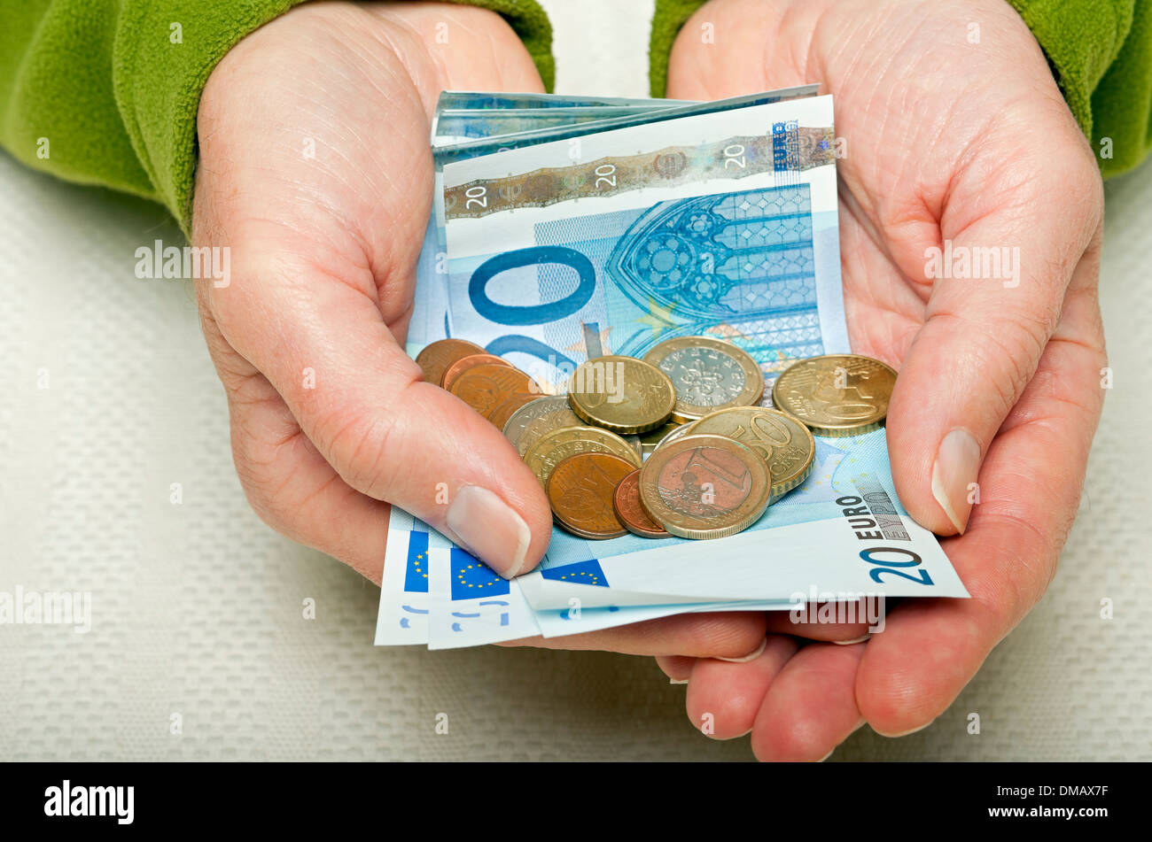 Hands holding 20 Euro notes and coins - Stock Image