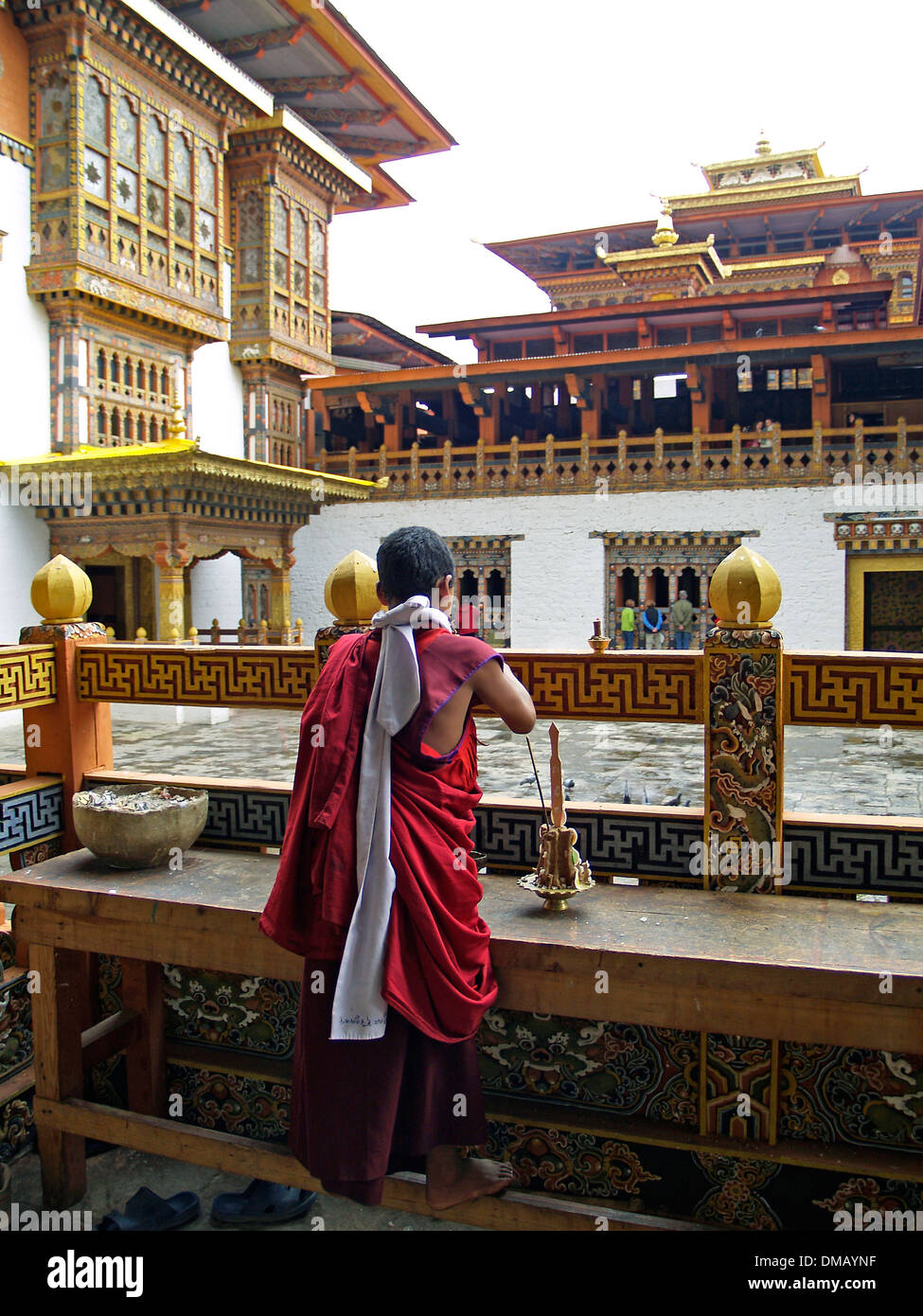 A young monk does a devotional in the courtyard of the Punakha Dzong,Bhutan - Stock Image