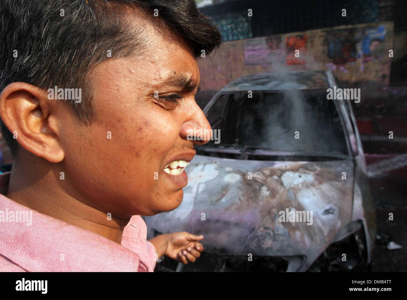 Dhaka, Bangladesh. 13th December 2013. A Bangladeshi vehicle owner reacts near a burning car set on fire by demonstrating Stock Photo