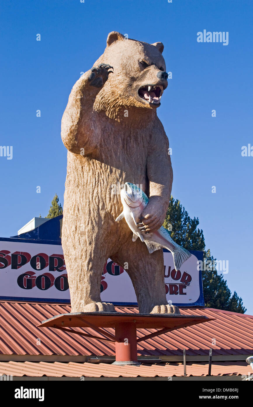 A grizzly bear with a salmon atop a sporting goods store in Gilchrist, Oregon - Stock Image