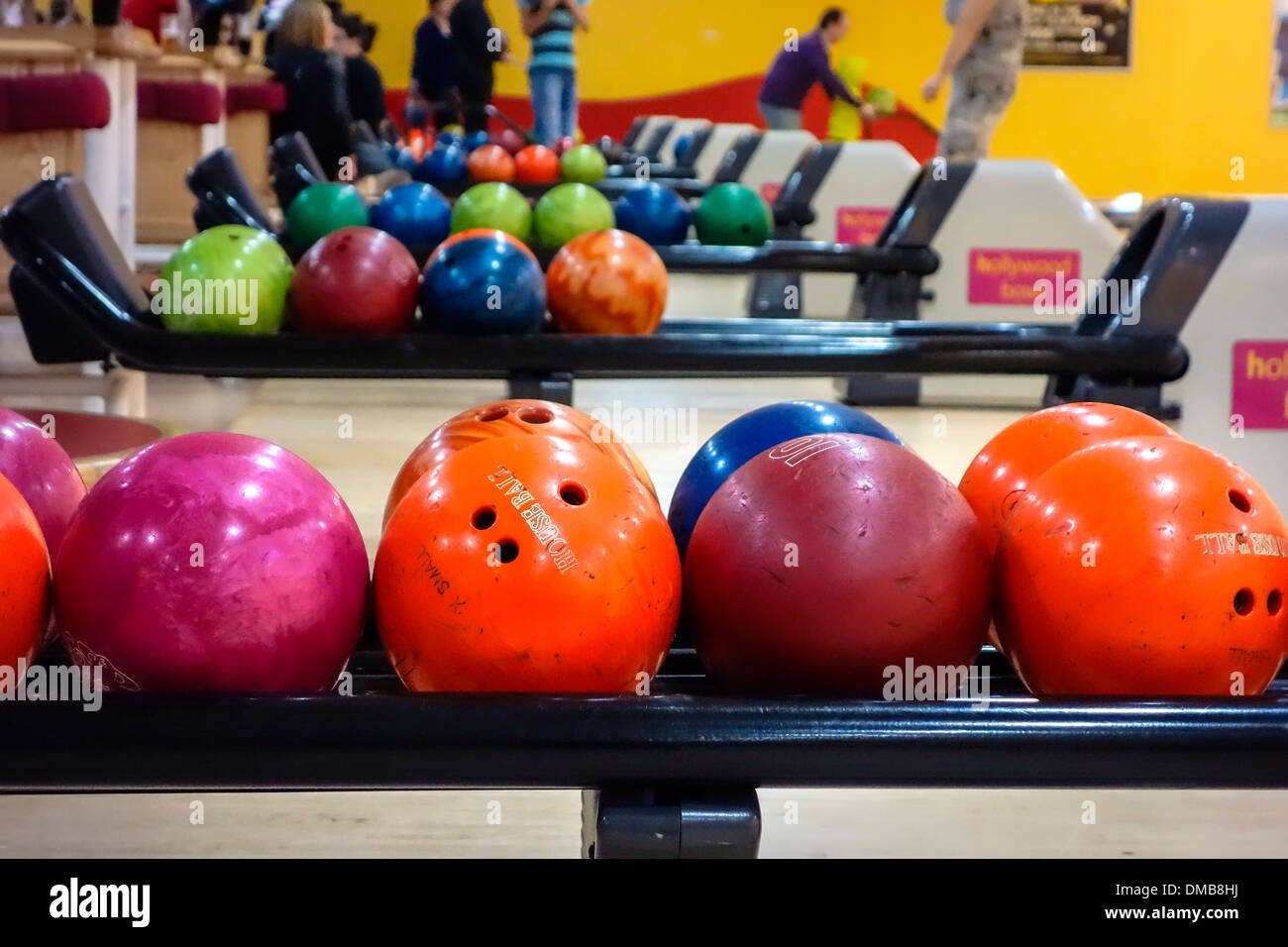 Colourful bowling balls lined up on rack ready for play. - Stock Image
