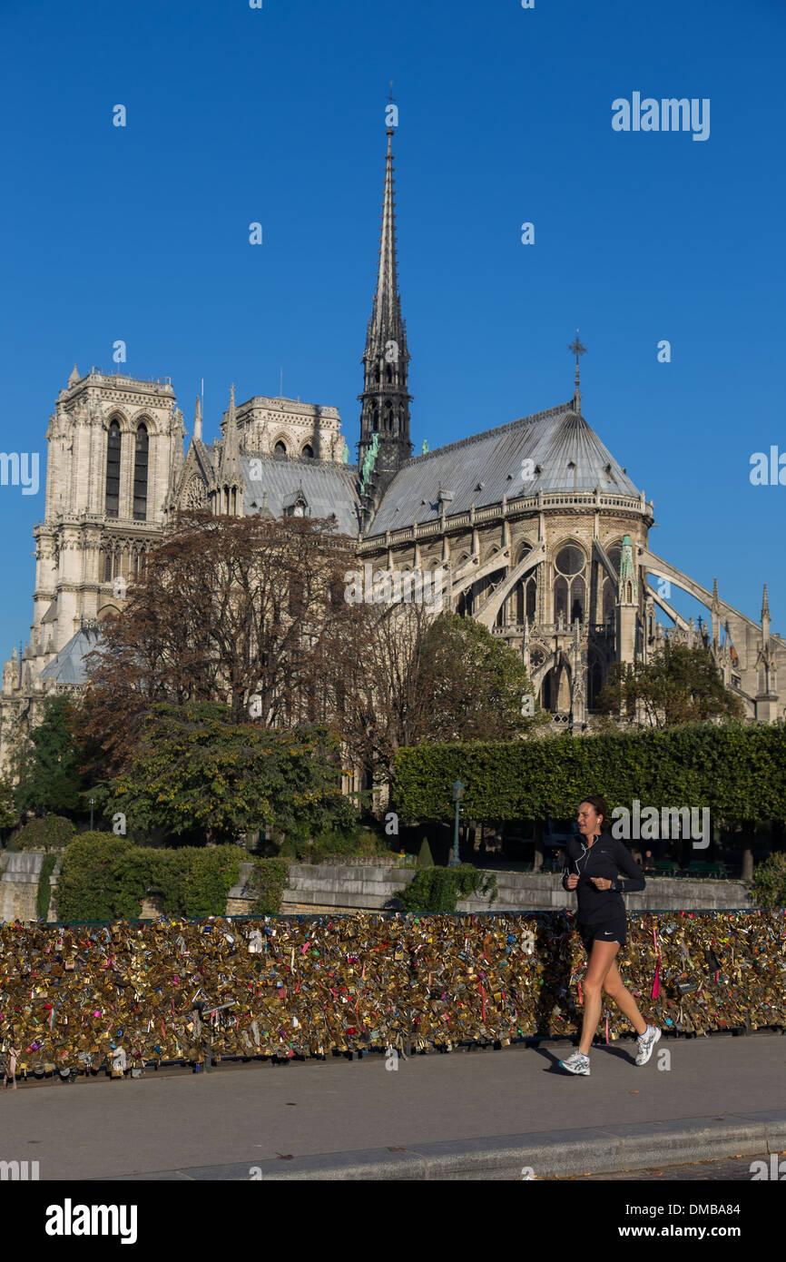 JOGGER AND LOVE PADLOCKS ON THE PONT DE L'ARCHEVECHE BRIDGE NEAR THE CATHEDRAL NOTRE-DAME DE PARIS, 4TH ARRONDISSEMENT, PARIS (75), FRANCE - Stock Image