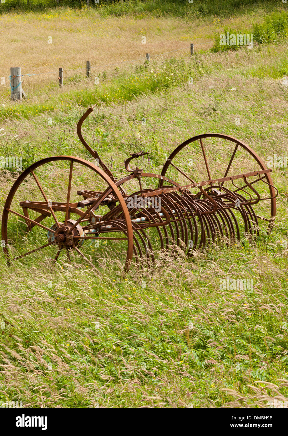 An abandoned rusting vintage agricultural hay rake - Stock Image