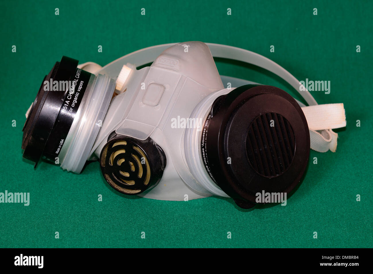 Half face protective safety mask or respirator on green background - Stock Image