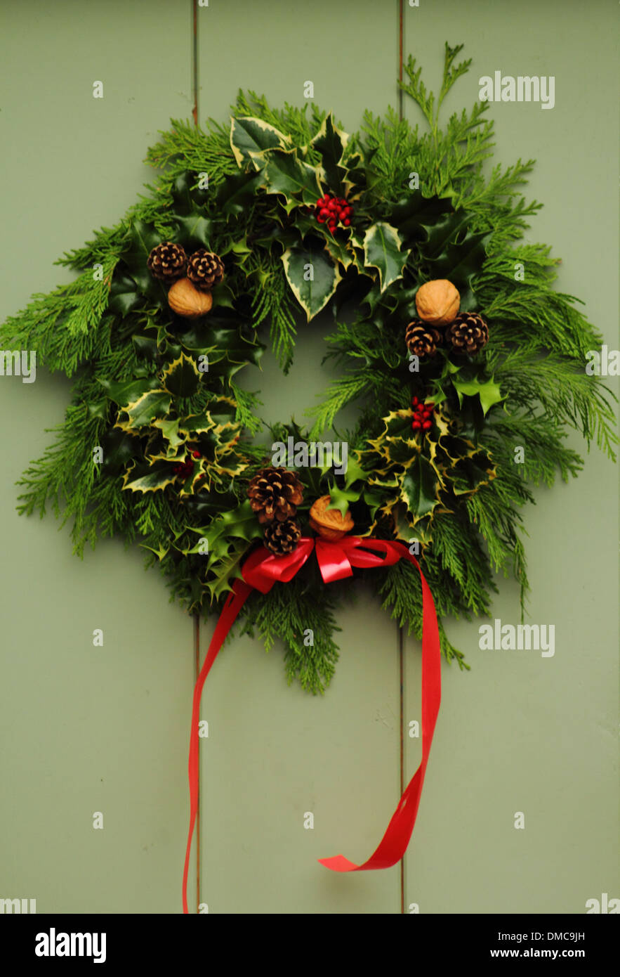 Christmas Wreath Hanging On Front Door Of Traditional English Stock