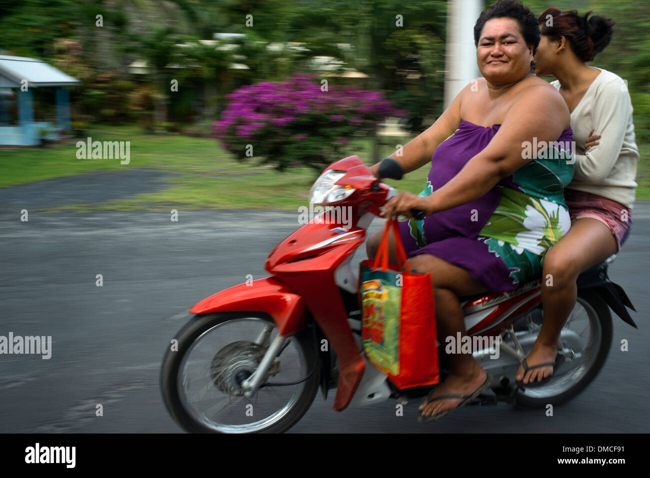 Rarotonga Island. Cook Island. Polynesia. South Pacific Ocean. Two obese people drive a motorcycle on a road on the island - Stock Image