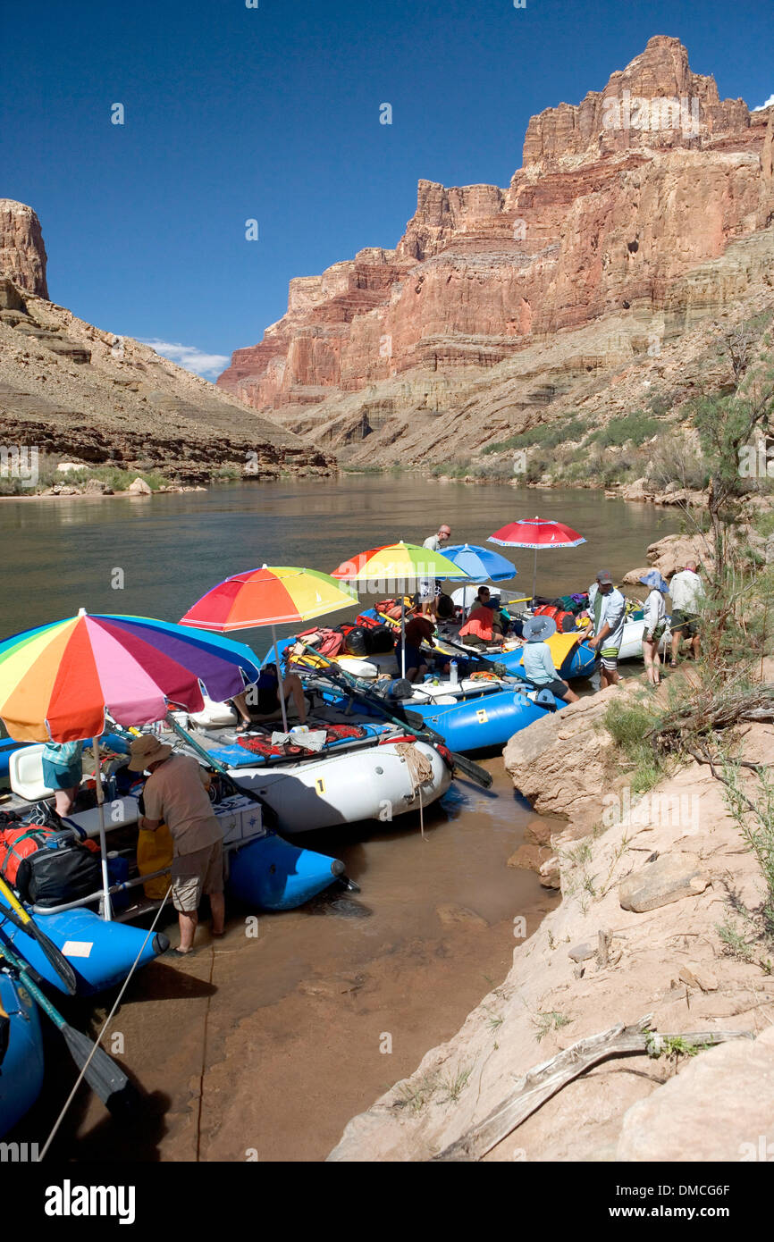 White water rafts with colorful umbrellas tied up alongside the Colorado River during a 21 day Grand Canyon adventure - Stock Image