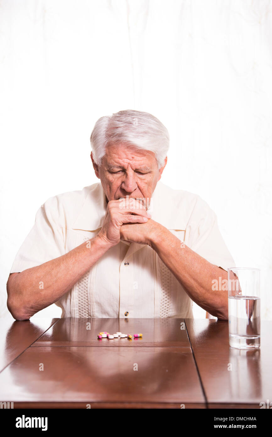 Ederly man preparing to take his medication - Stock Image