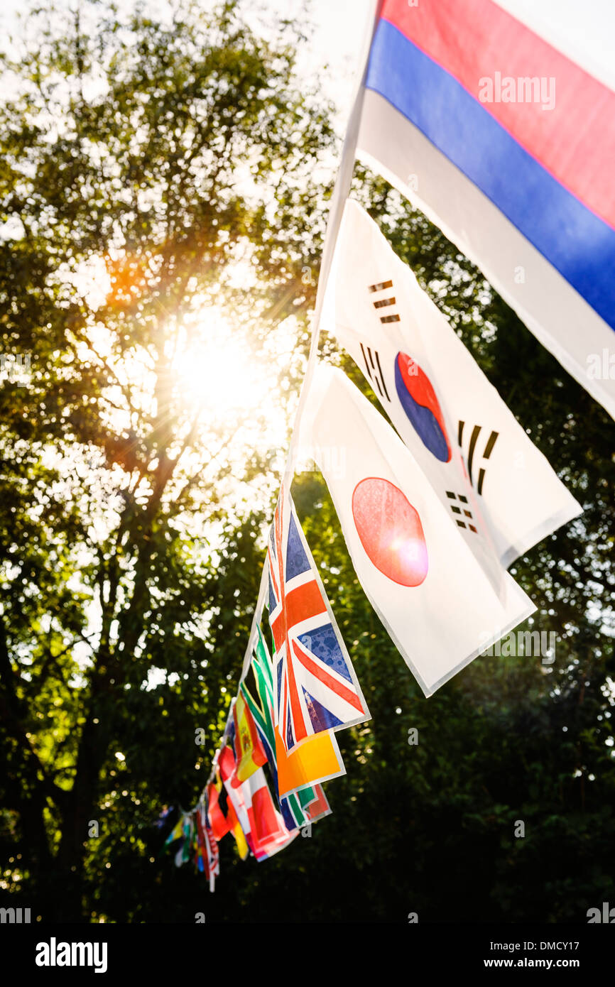 Multinational flags on a string at a garden party. - Stock Image