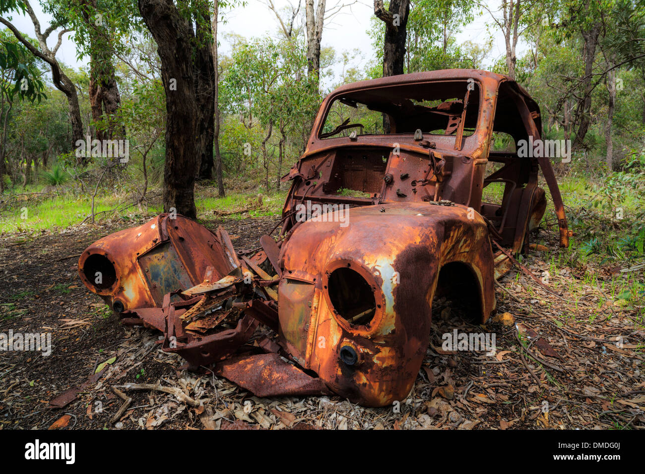 The rusted wreck of an abandoned  car in Australian bushland. - Stock Image