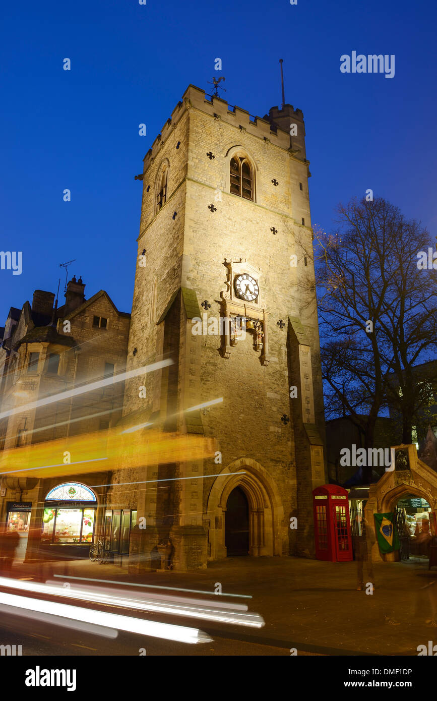 Carfax Tower in Oxford city centre lit up at night as traffic drives past - Stock Image
