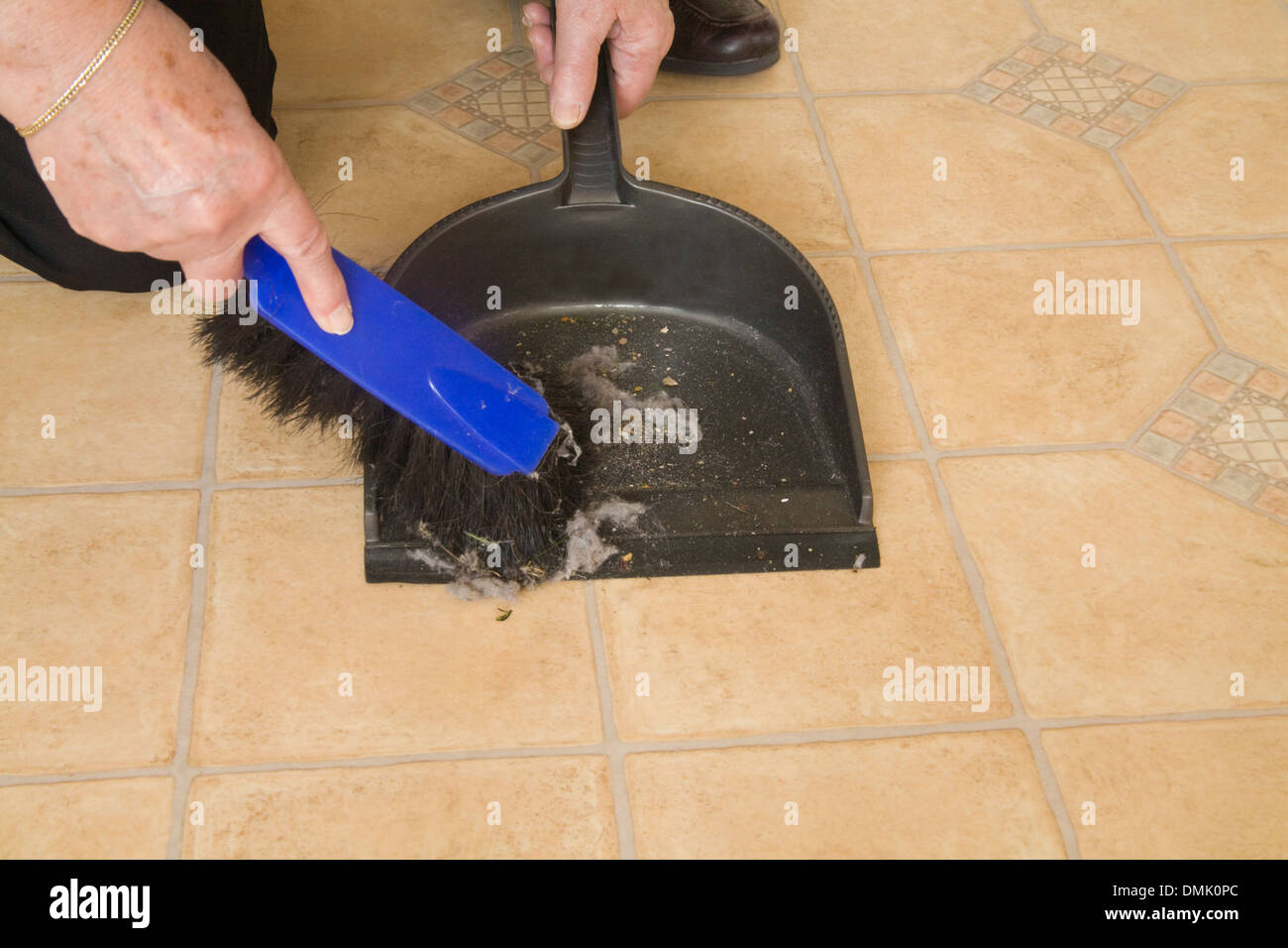 Close up woman kneeling sweeping fluff and dirt off a kitchen floor with hand brush into dustpan - Stock Image