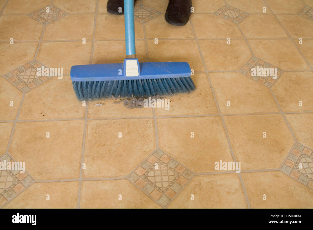 Close up woman sweeping fluff and dirt off a kitchen floor - Stock Image