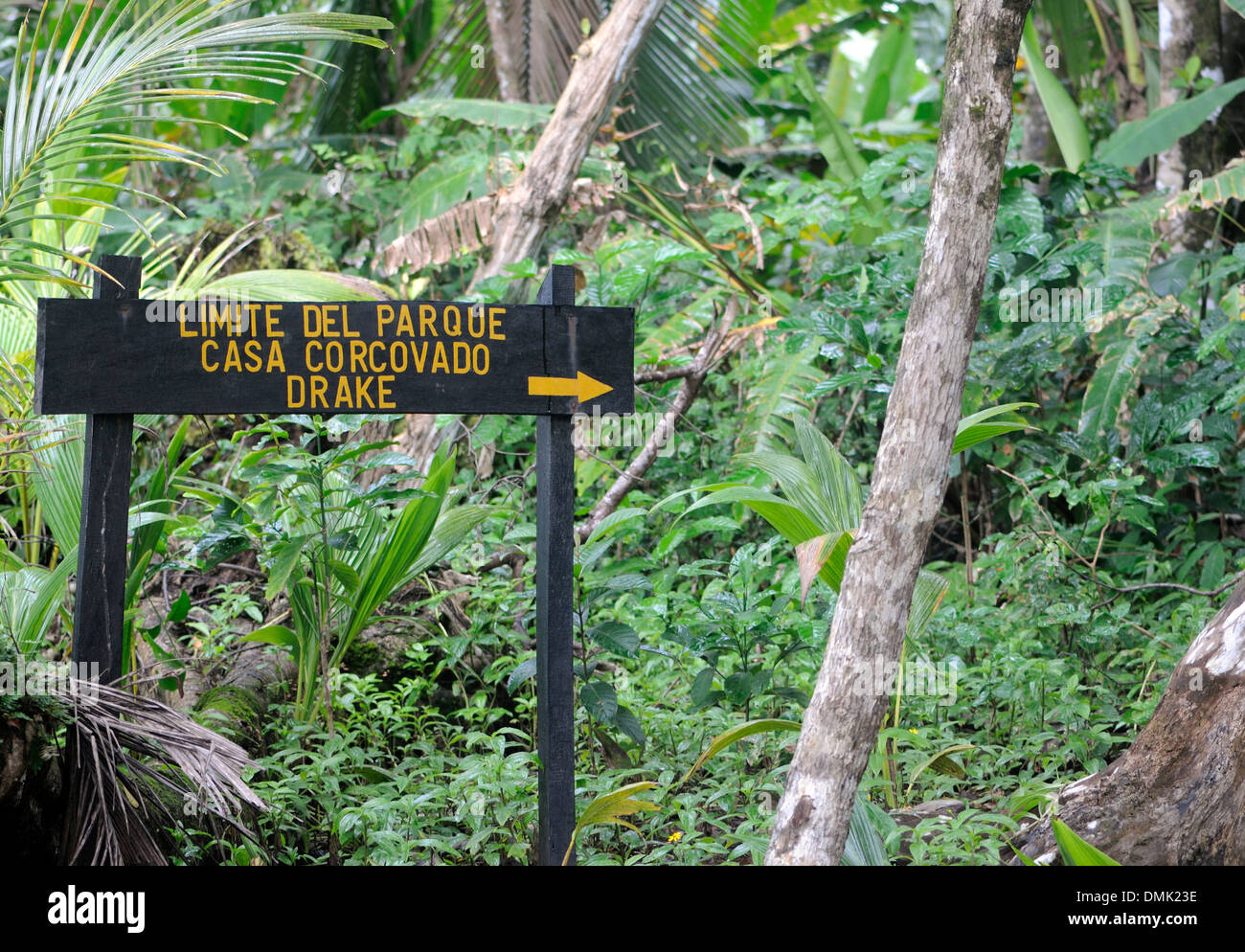 A sign marking the boundary of the  Corcovado National Park and showing the path to Drake Bay and Casa Corcovado. Oro Peninsula. - Stock Image