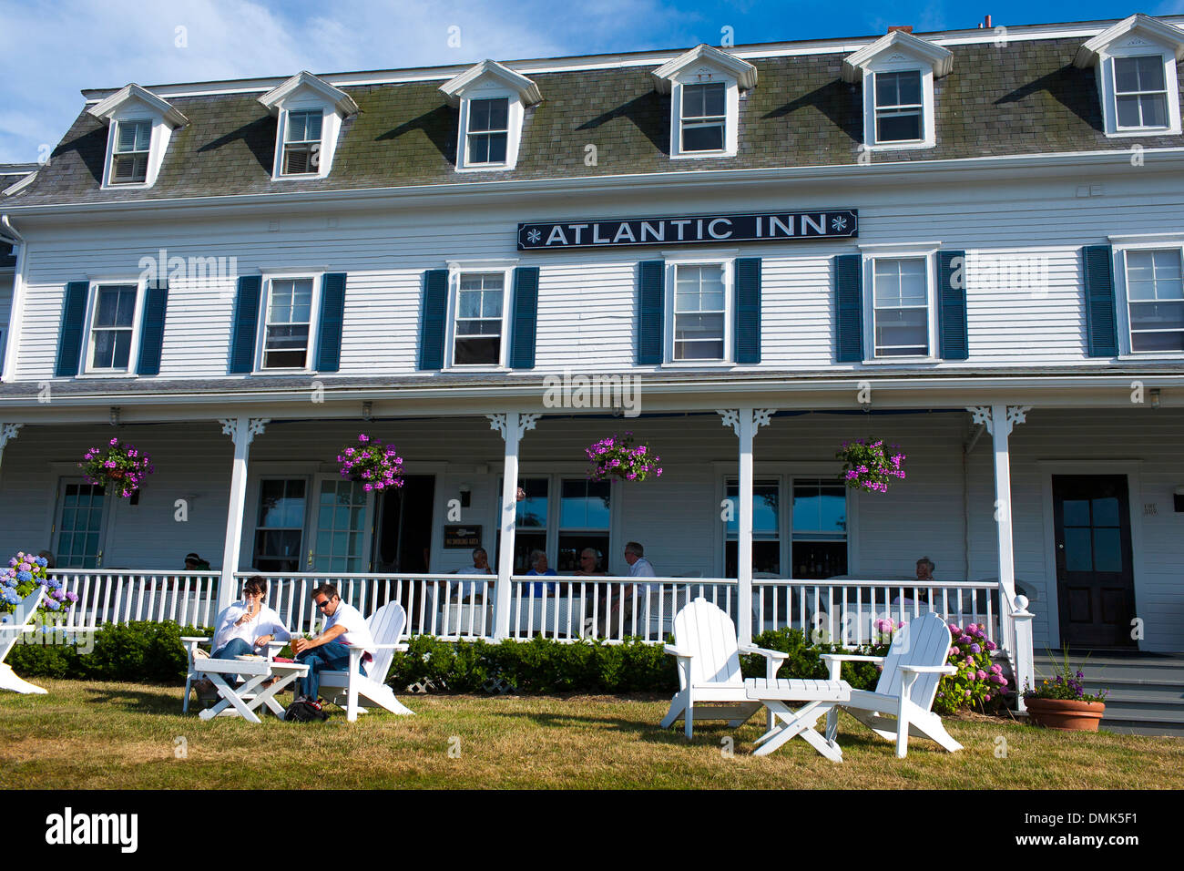 A young couple drink and eat in front of the Atlantic Inn Hotel on Block Island, a popular tourism destination in Rhode Island - Stock Image