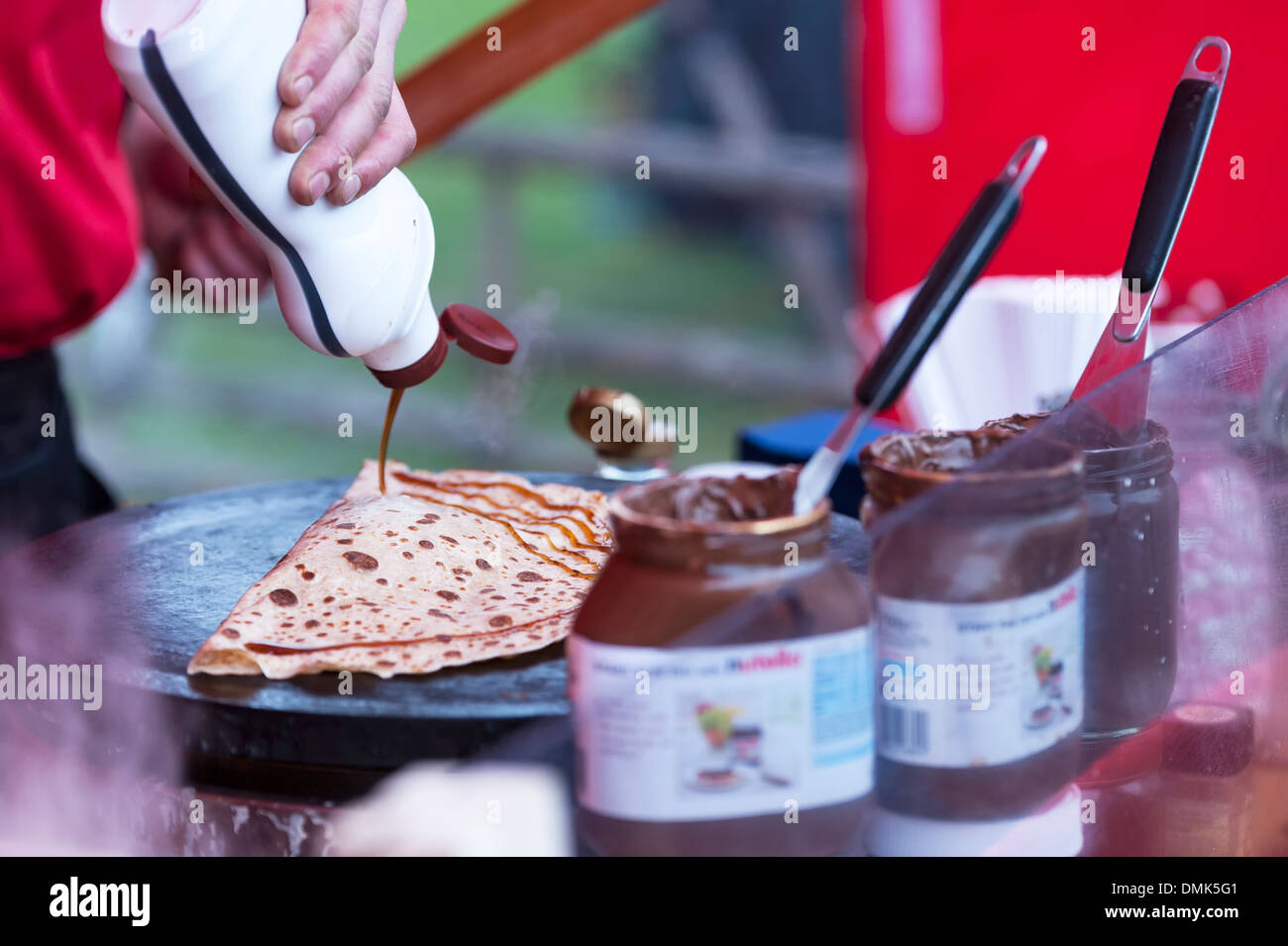 A male hand pouring syrup onto sweet crepe pancake that are being made and sold at a creperie take away market stall trade stand - Stock Image