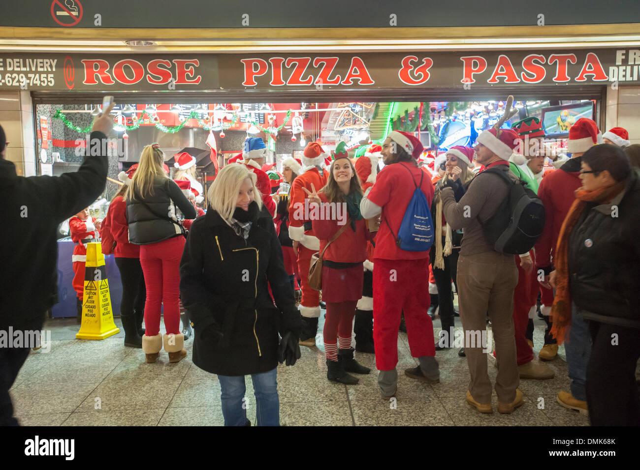 32392114 New York, USA. 14th December 2013. Christmas revelers arrive at  Pennsylvania Station for
