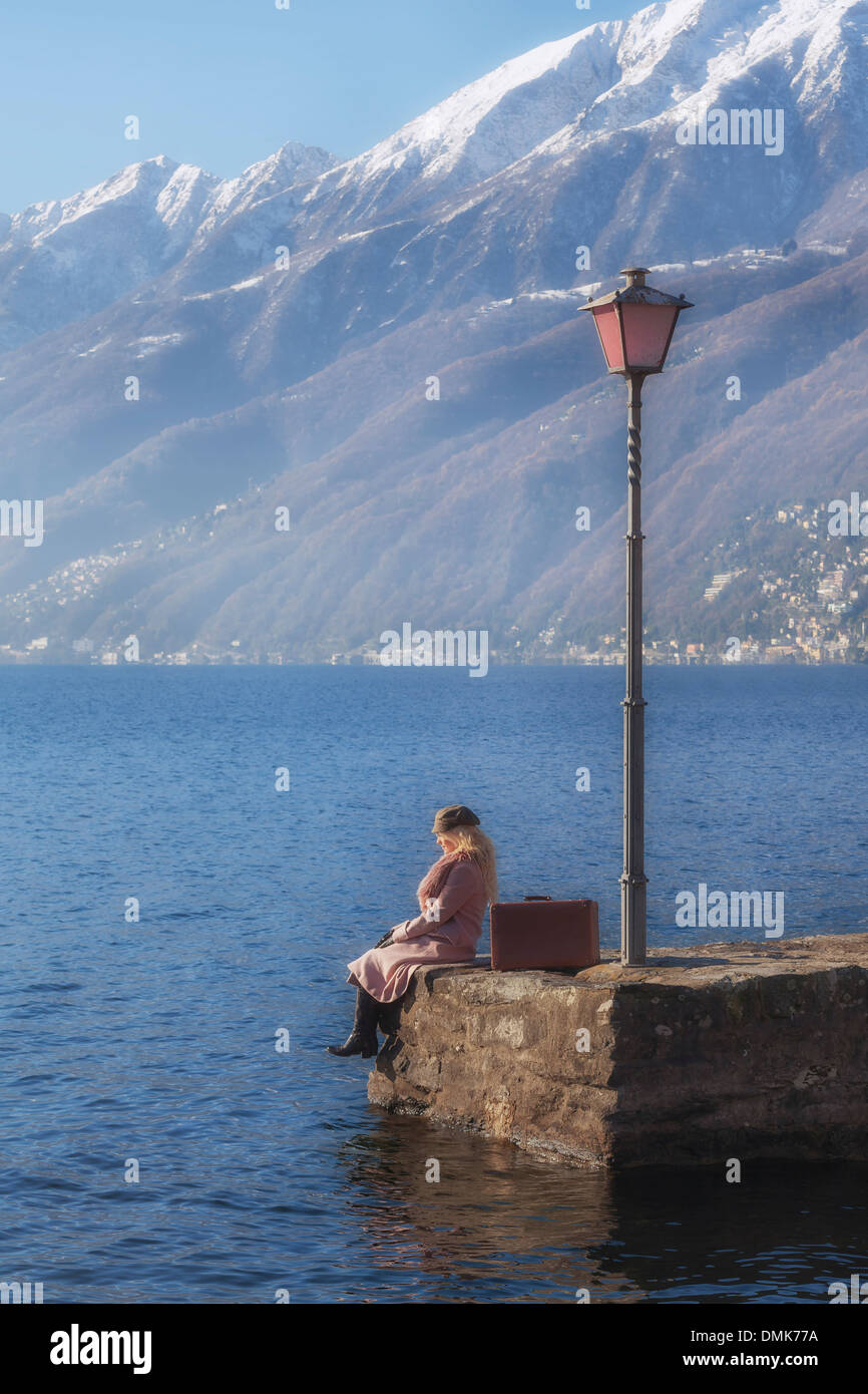 a woman in a pink coat is sitting on a jetty at a lake - Stock Image