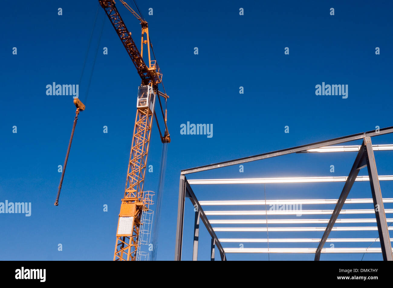 Tower crane and new warehouse roofing steelwork / factory building site - France. - Stock Image