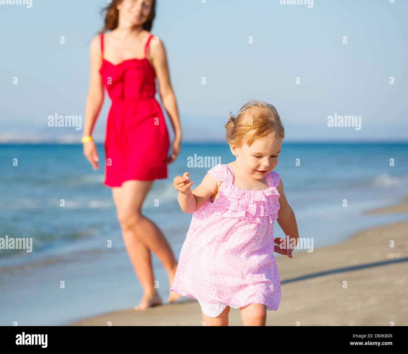 Little girl running on the beach Stock Photo
