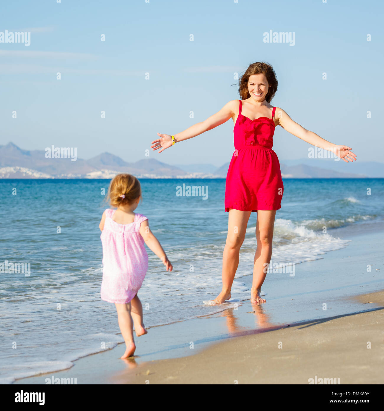 Little girl playing on the beach - Stock Image
