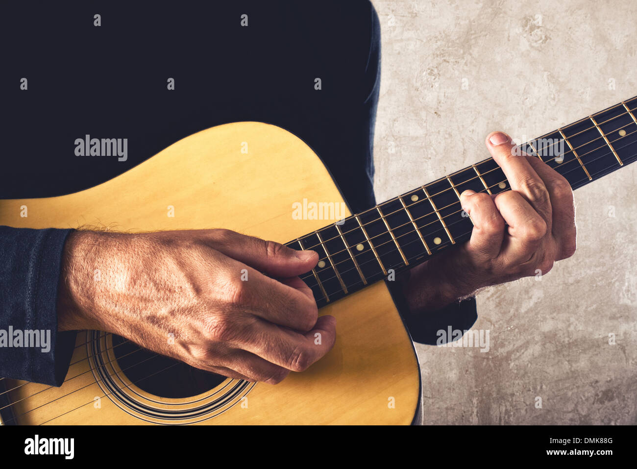 Man playing acoustic guitar, unplugged performance. - Stock Image