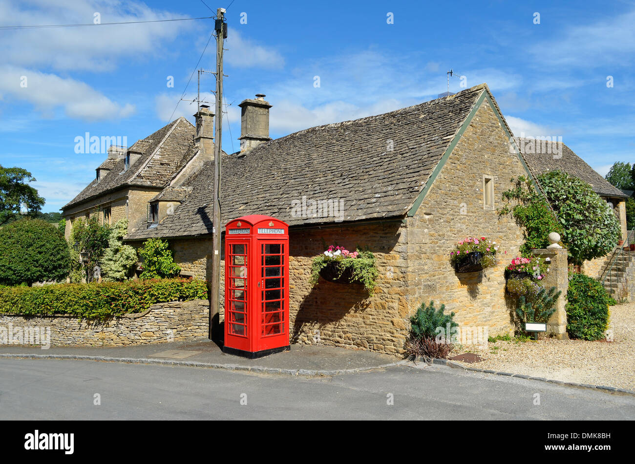 Honey coloured stone houses and a red telephone box in a village in the Cotswolds in rural England. - Stock Image