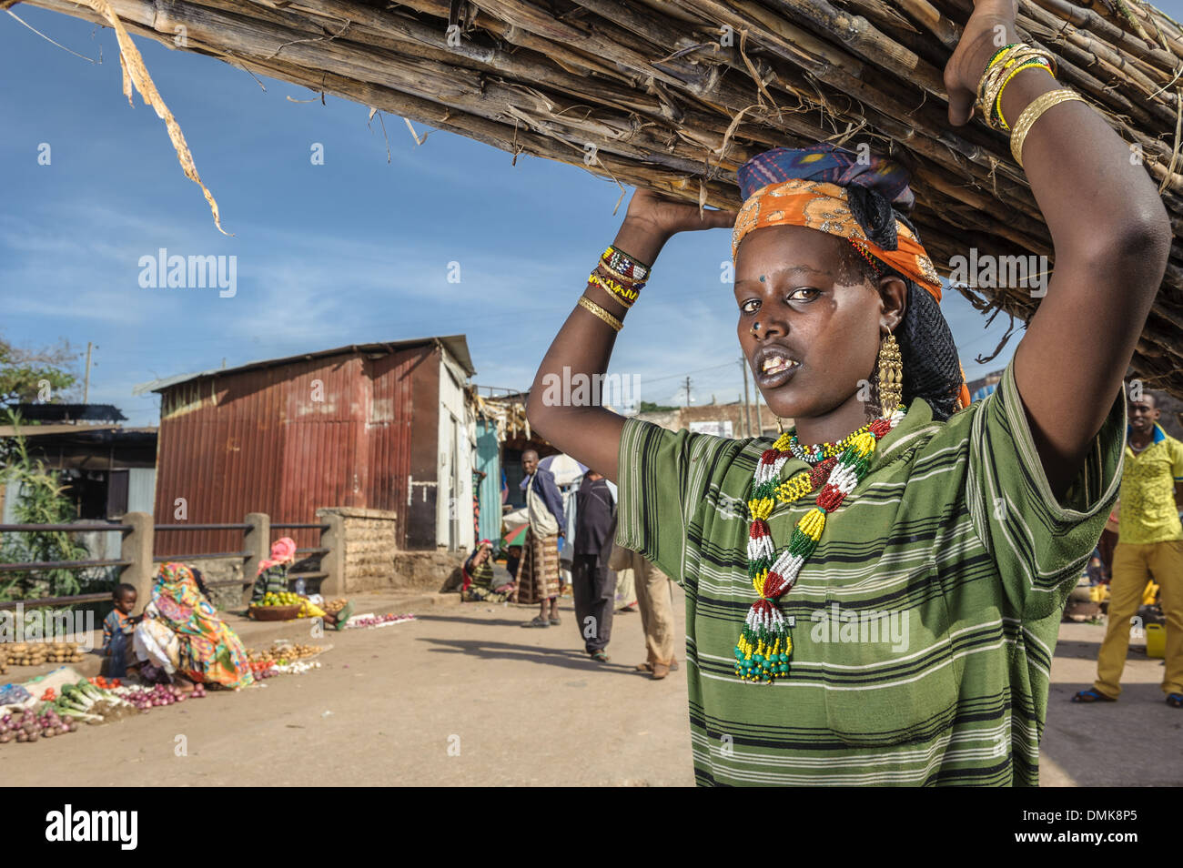 Young woman carrying a bunch of sugarcane on her head, Harar, Ethiopia, Africa - Stock Image
