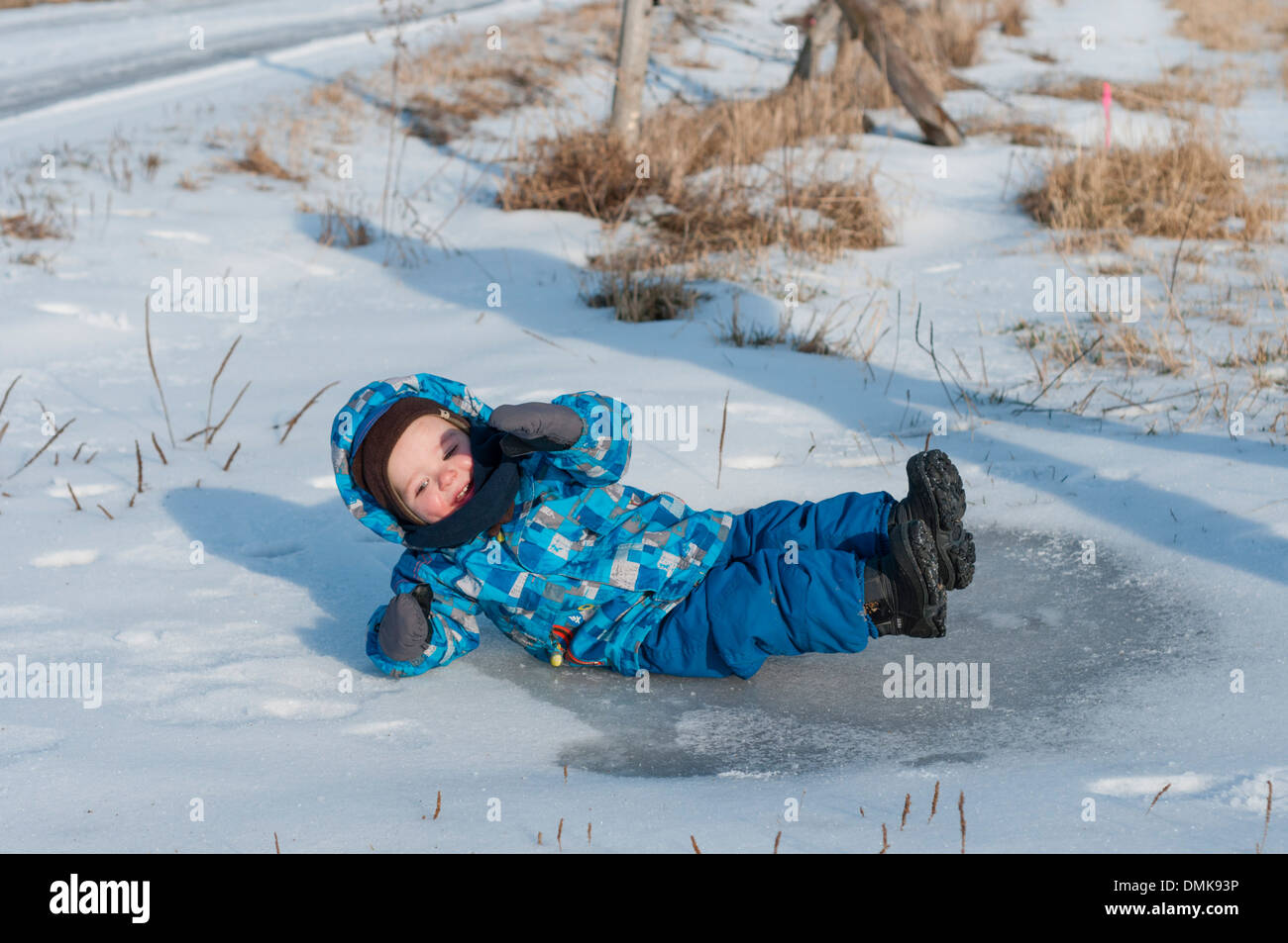 A baby boy slips on an icy puddle - Stock Image