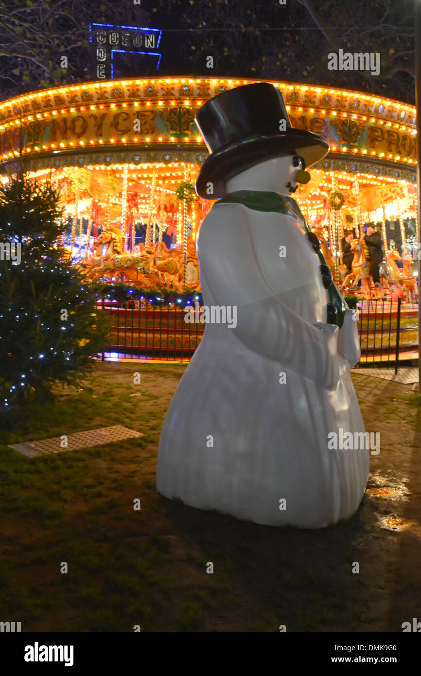 Leicester Square Christmas fairground at night with large snowman - Stock Image