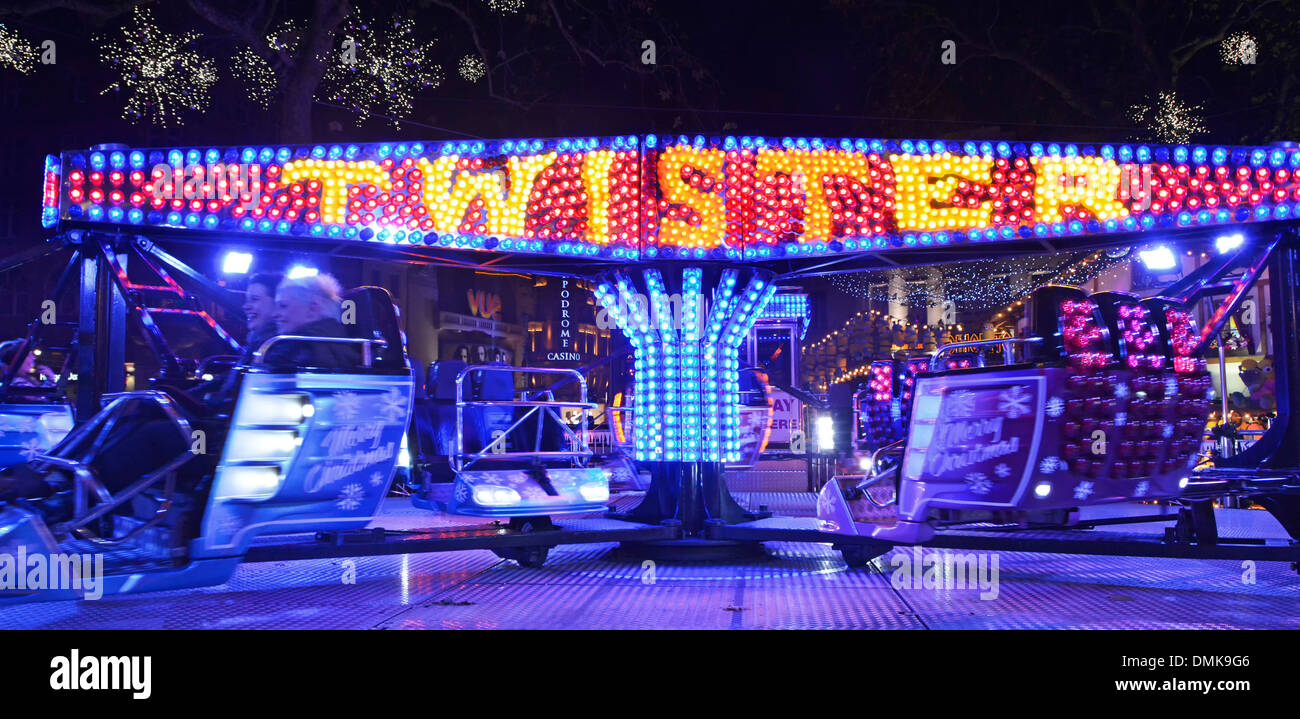 Leicester Square Christmas fairground at night with people on Twister ride - Stock Image