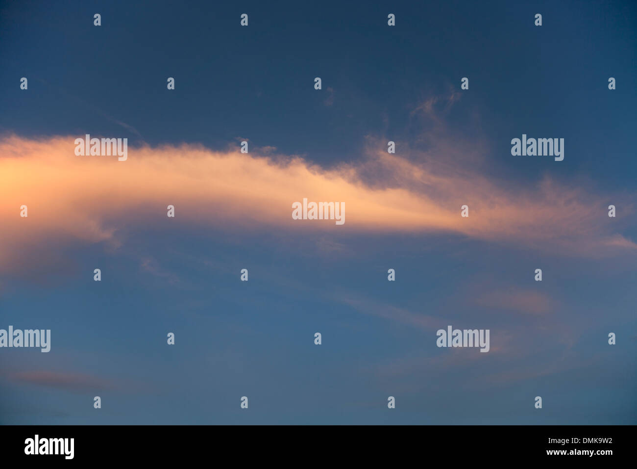 Wispy cloud formations catching the colours of the setting sun. - Stock Image