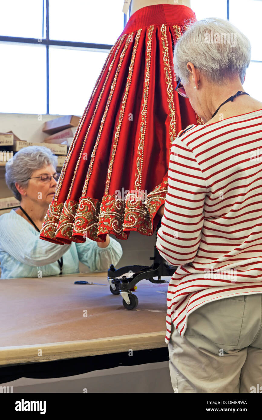 Seamstresses working on red skirt for The Pearl Fishers, Santa Fe Opera, Santa Fe, New Mexico USA - Stock Image