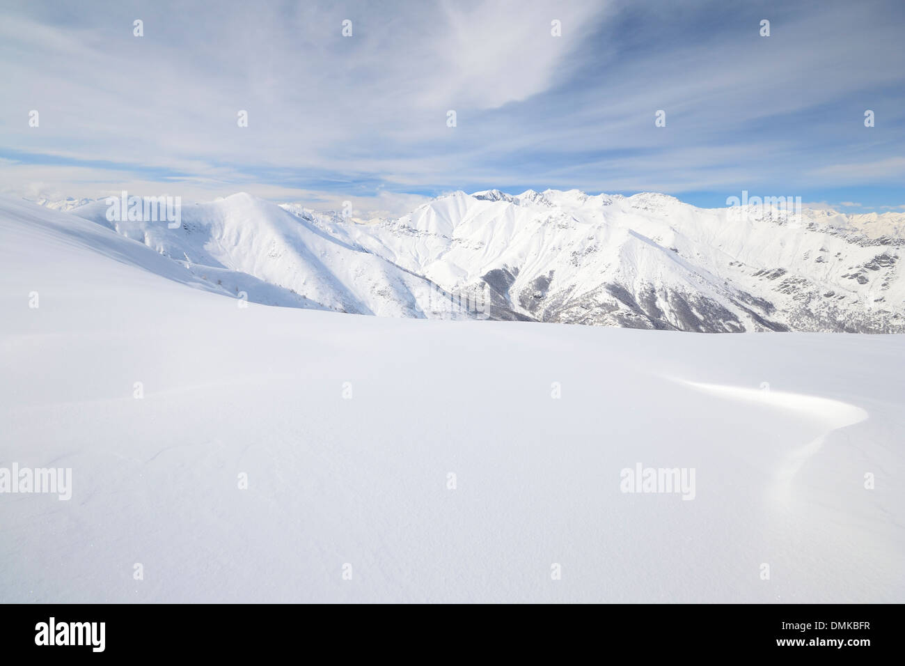 Candid off-piste ski slope in scenic background of high mountain peak - Stock Image