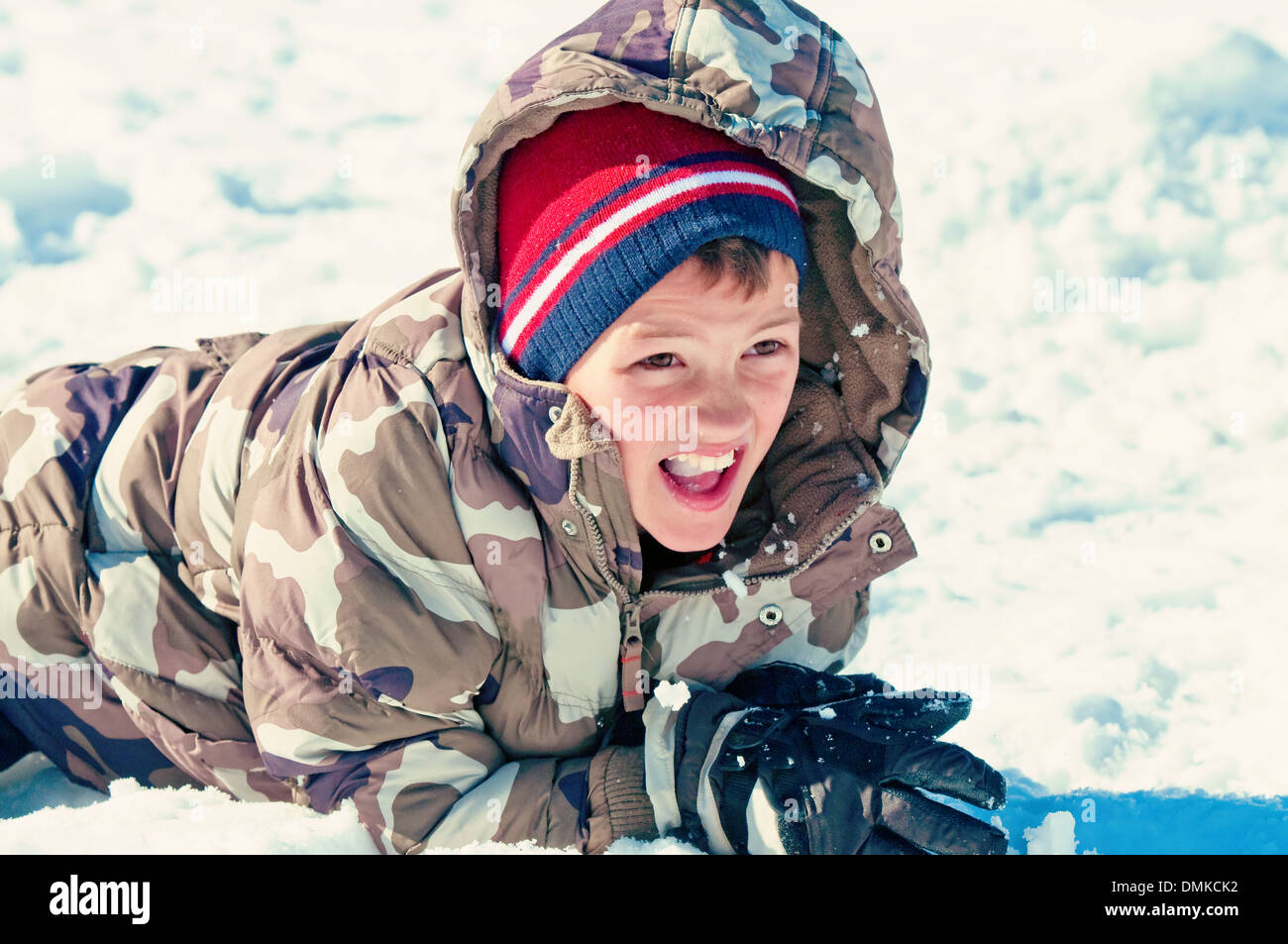 5d905f0de cute boy in camouflage jacket laying in the snow Stock Photo ...