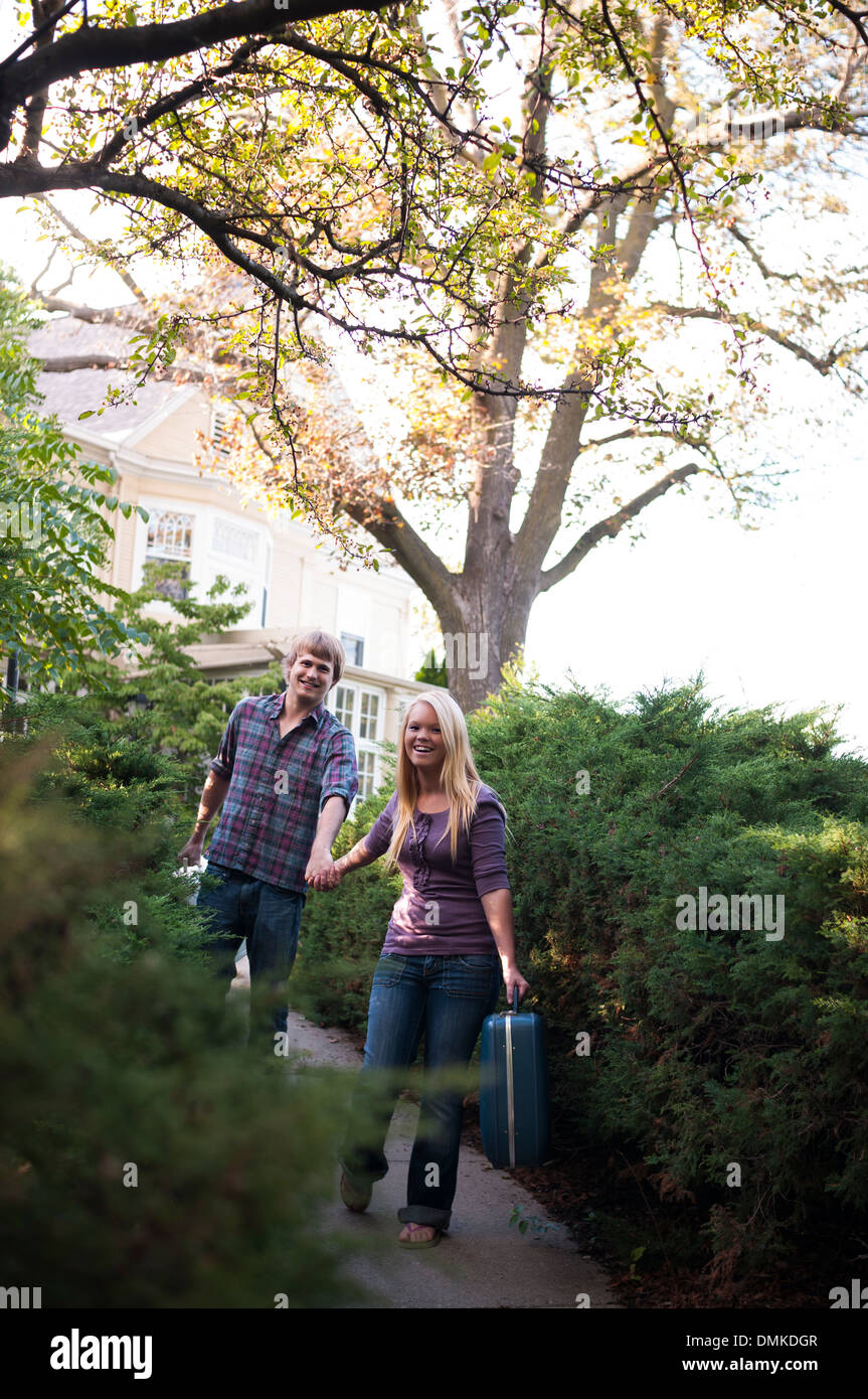 Young couple running away from home. - Stock Image