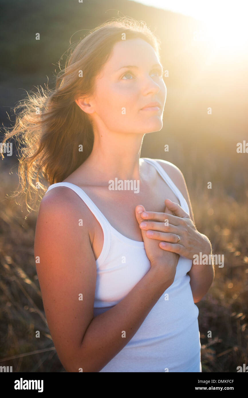 Beautiful young woman with her hands on her chest looking gratefully towards the sky. - Stock Image