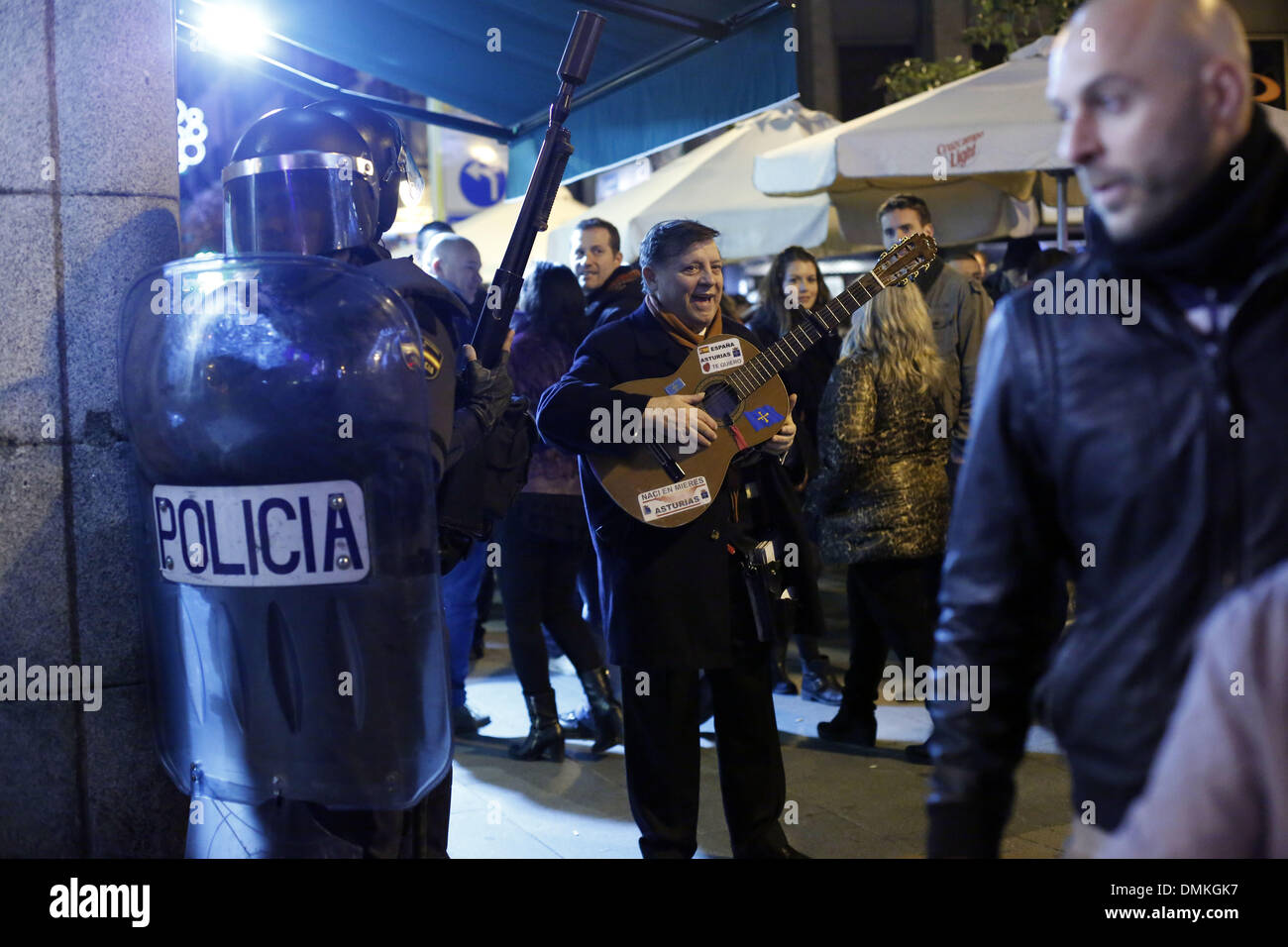 Madrid, Spain. 14th Dec, 2013. A man plays the guitar while riot police clear the street afte riots rnear parliament in Madrid, Saturday, Dec. 14, 2013. Protesters, angry at draft legislation that aims to set heavy fines for offenses such as causing serious disturbances outside parliament, gathered near Spain's legislature under the gaze of a strong police presence. The protestopposes the introduction of a bill that will set fines of up to 30,000 euros ($40,800) for offenses such as burning the national flag and insultin Credit:  ZUMA Press, Inc./Alamy Live News - Stock Image