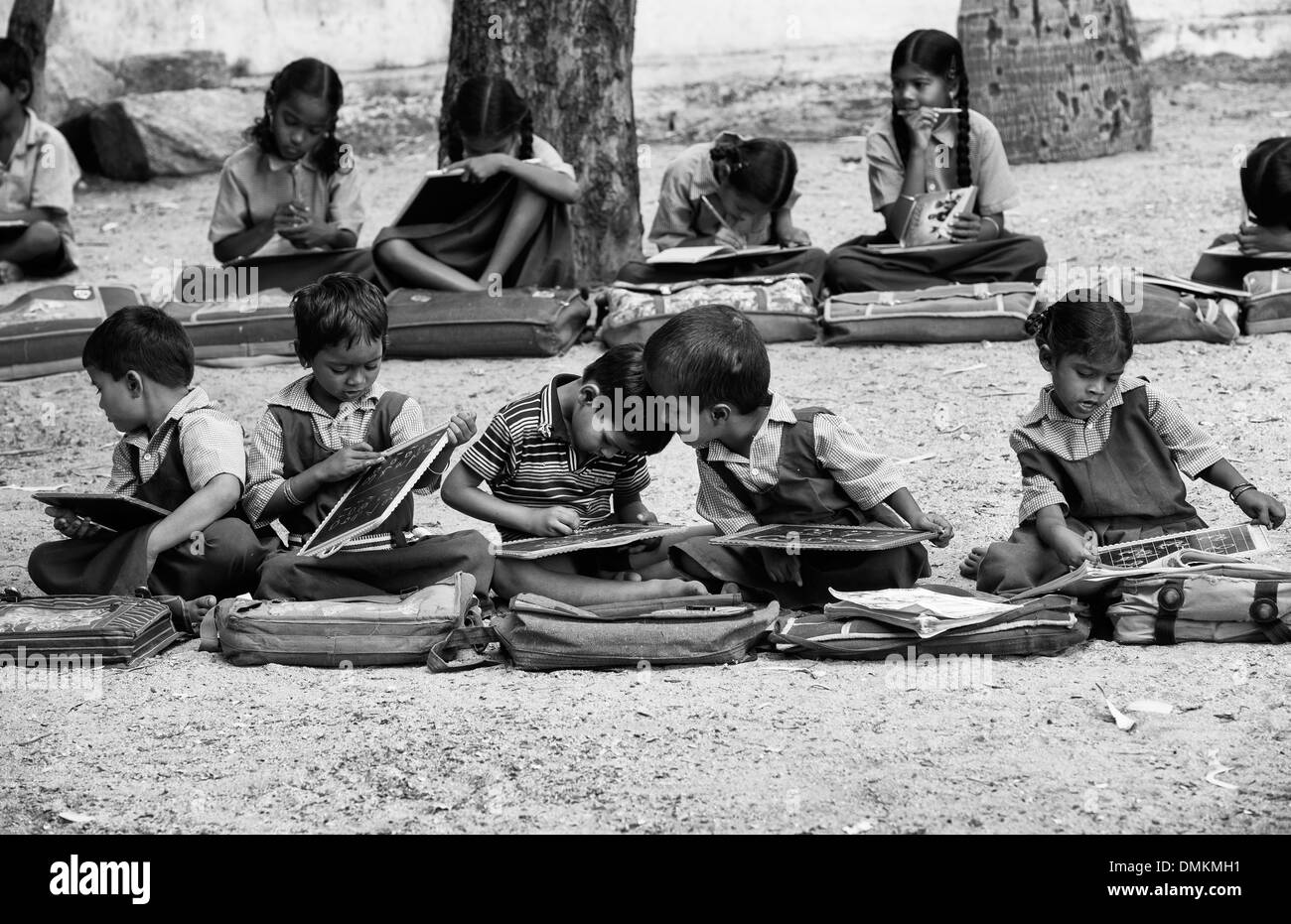 Rural indian village school children in an outside class writing on a chalk tablets andhra