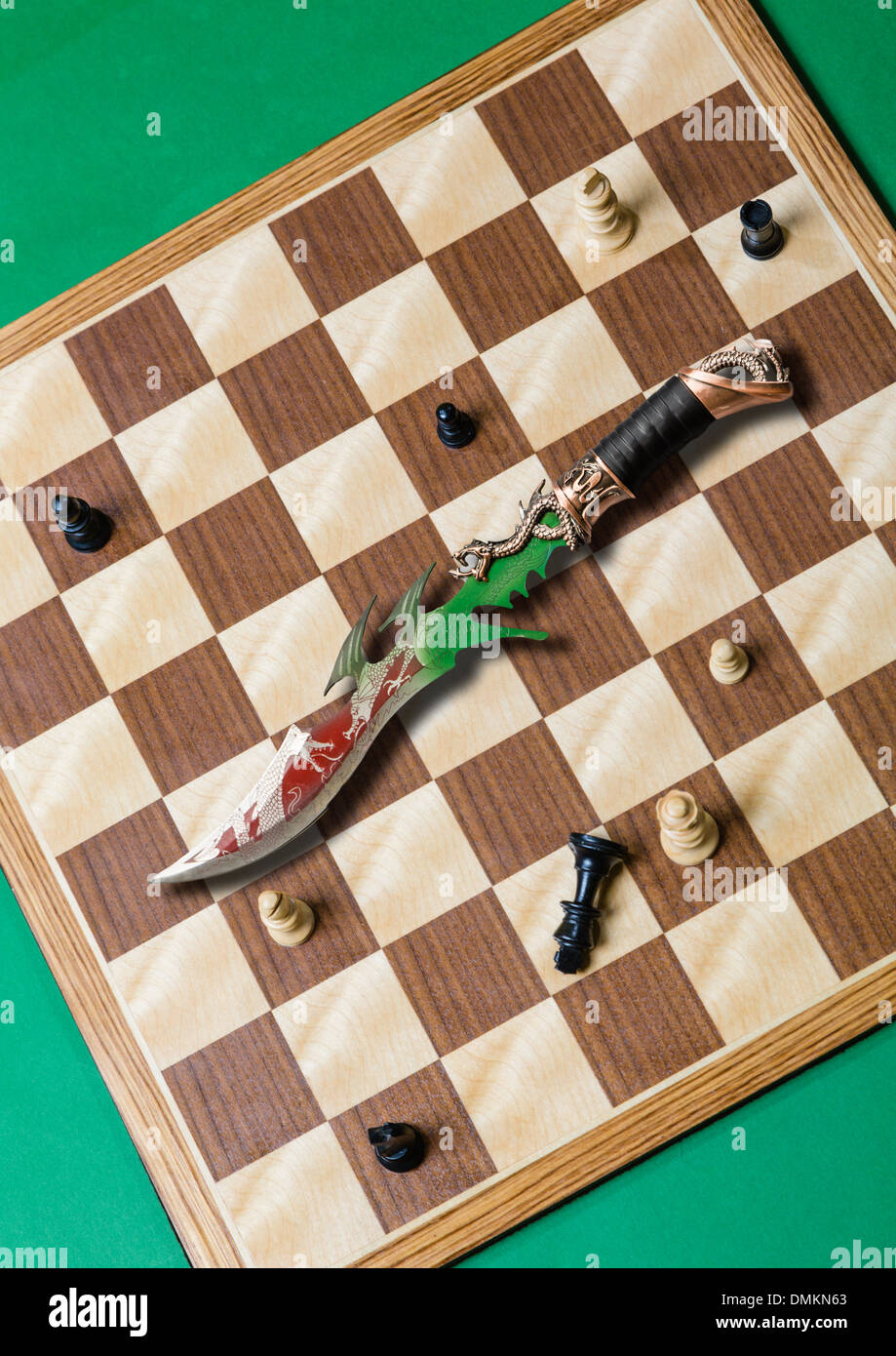 Chess board from above with ornate dagger on it.  Black king on its side.  Suitable for book cover or poster. - Stock Image