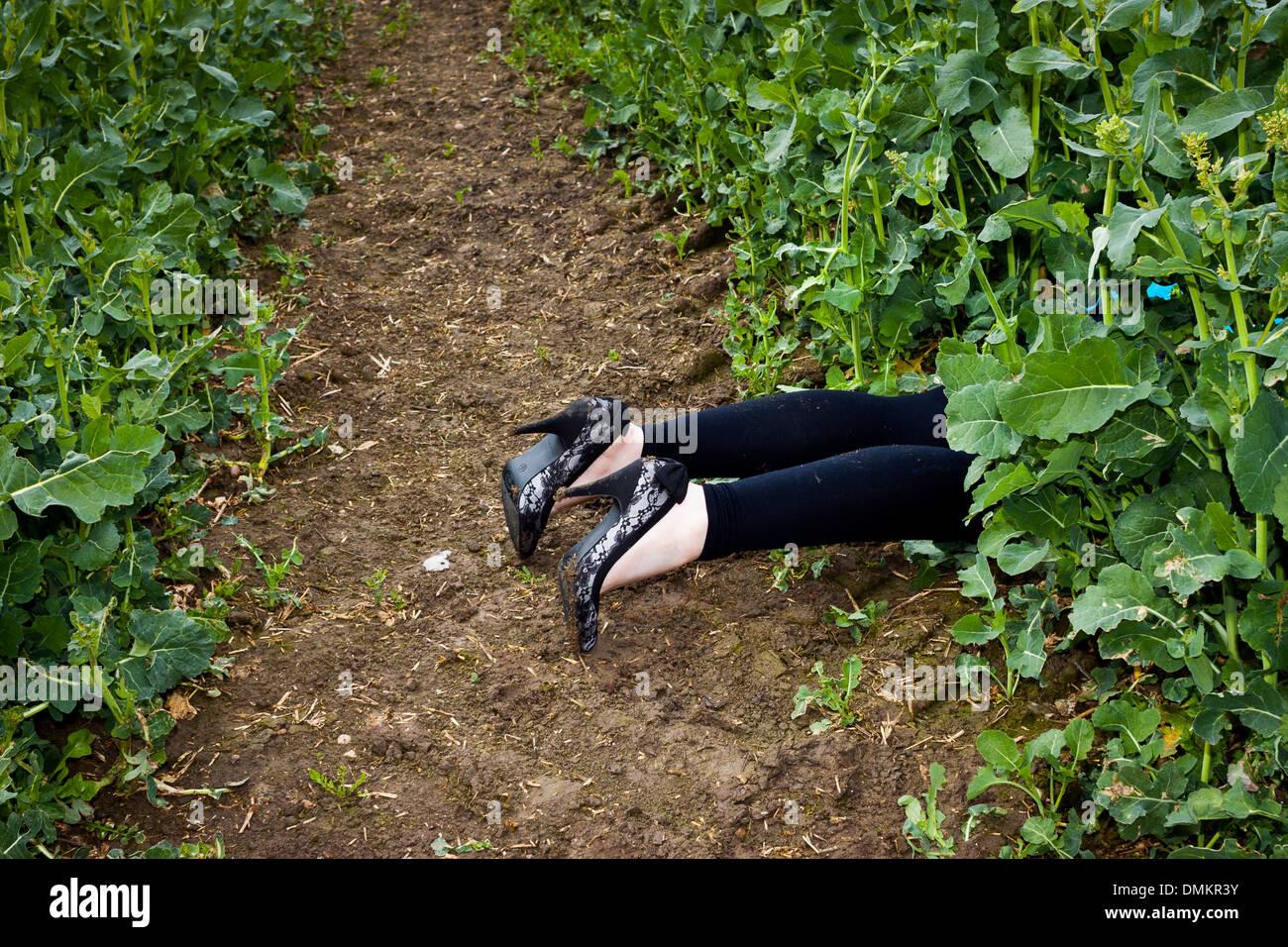 Legs in a field, suggestive of murder - Stock Image