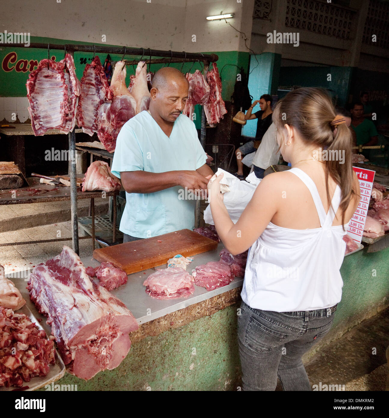 Woman buying meat from a butcher stall, Cienfuegos indoor market, Cuba, caribbean - Stock Image